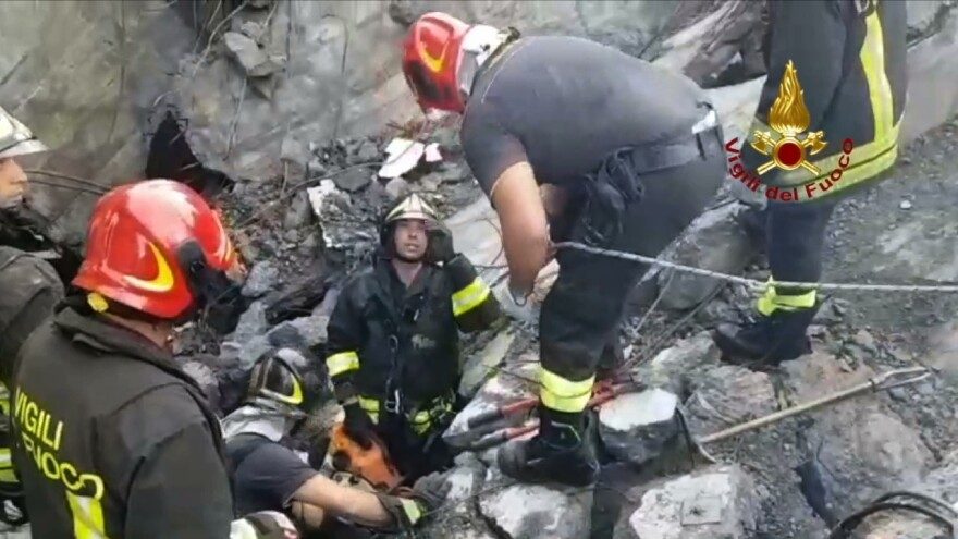 Italian firefighters work at the collapsed Morandi highway bridge in Genoa on Tuesday.