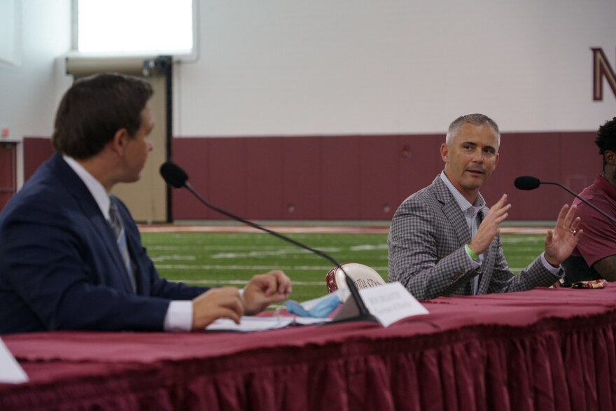 Florida State University head football coach Mike Norvell talks with Governor Ron DeSantis during a roundtable discussion held at FSU's football practice facility on August 11, 2020.