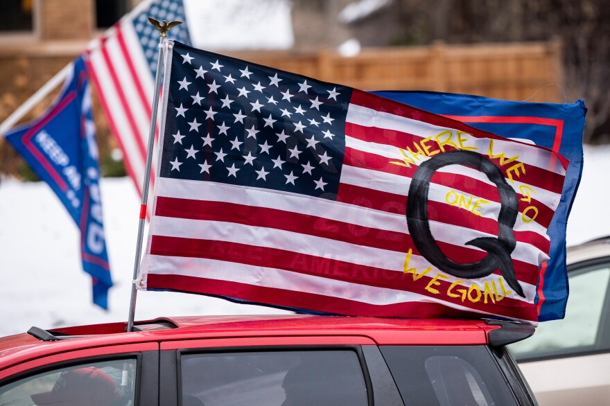 A car with a flag endorsing the QAnon conspiracy theory drives by as supporters of President Donald Trump gather for a rally outside the Governor's Residence on Nov. 14 in St. Paul, Minn.