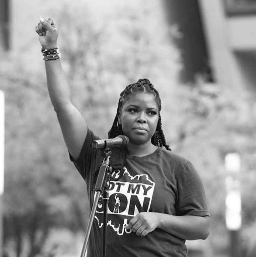 black and white photo of Tramonica Brown with her fist raised at a protest.