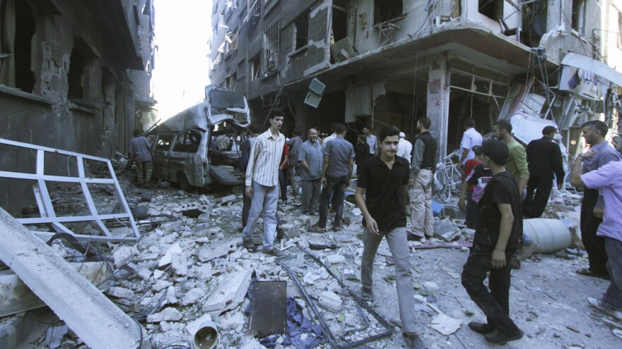 Syrians inspect a site hit by what they said were airstrikes carried out by President Bashar Assad in the Eastern Ghouta area on Aug. 3. Assad's forces continue to besiege the area near Damascus, which is still controlled by rebels.