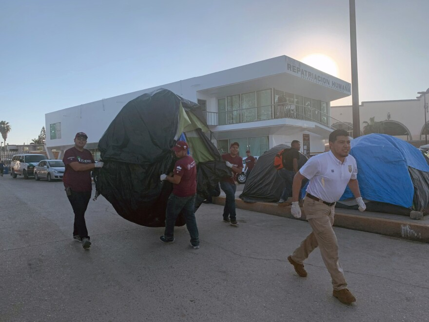 A Mexican official and volunteers help move someone's tent from an encampment to large Mexican government tent structures near the Rio Grande.