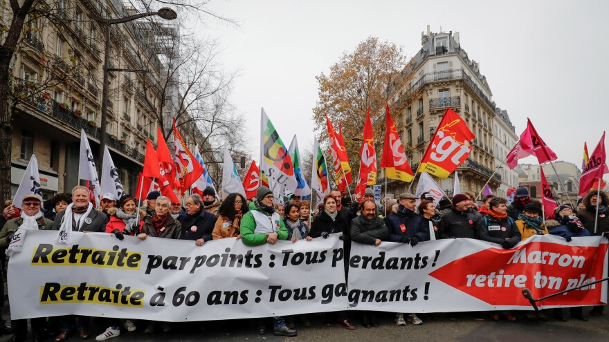 "People hold a banner reading ""Pension by points: we all lose. Retirement at 60: we all win"" during a demonstration against a plan to overhaul national pensions in Paris."