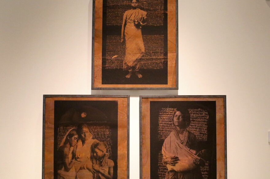 "A piece showing portraits of three unnamed Dalit women is called ""We are still here."" Their images are juxtaposed against legal texts from the 19th century governing their lives as women and as the lowest caste in Indian society."