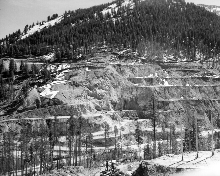 black-and-white photos of the Stibnite Mining district show road and mining scars on the landscape.