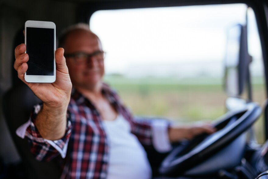 Photo of a man behind steering wheel holding out a smartphone.