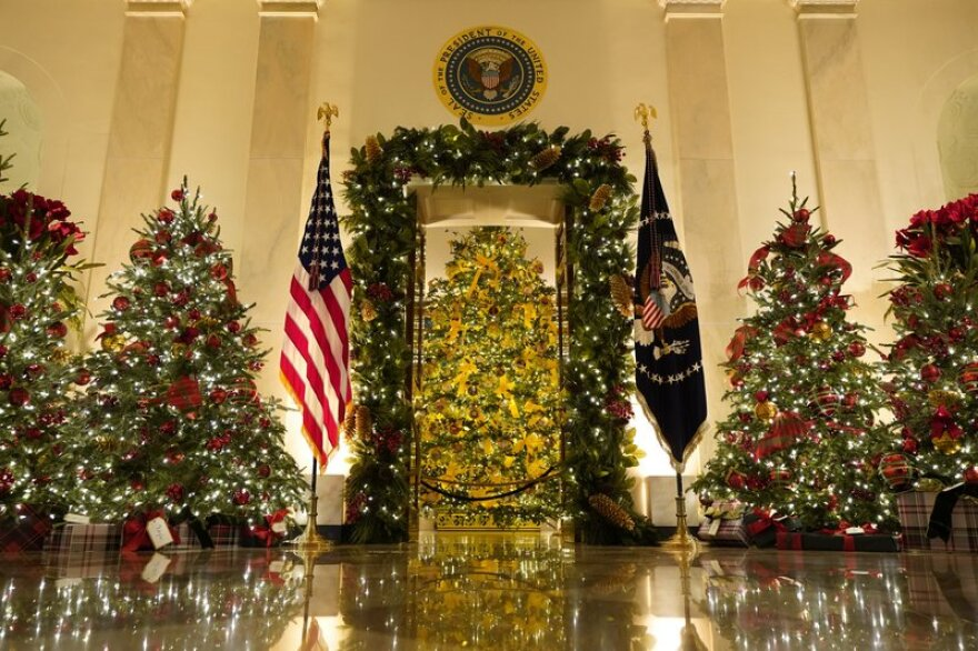 Brightly decorated Christmas trees adorn a room at the White House.
