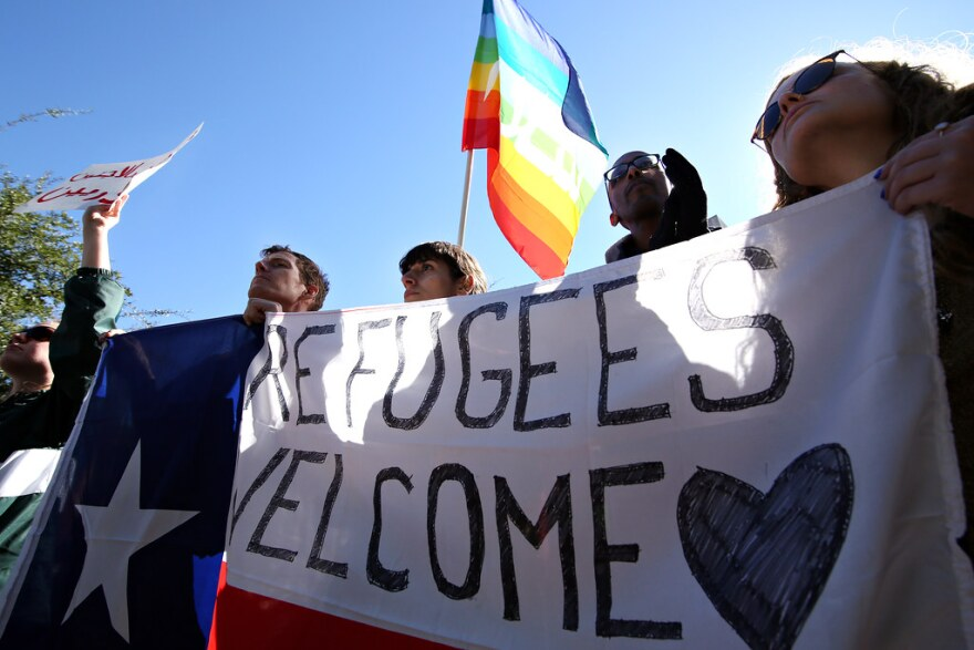 """Protesters hold a sign that says """"Refugees Welcome."""""""