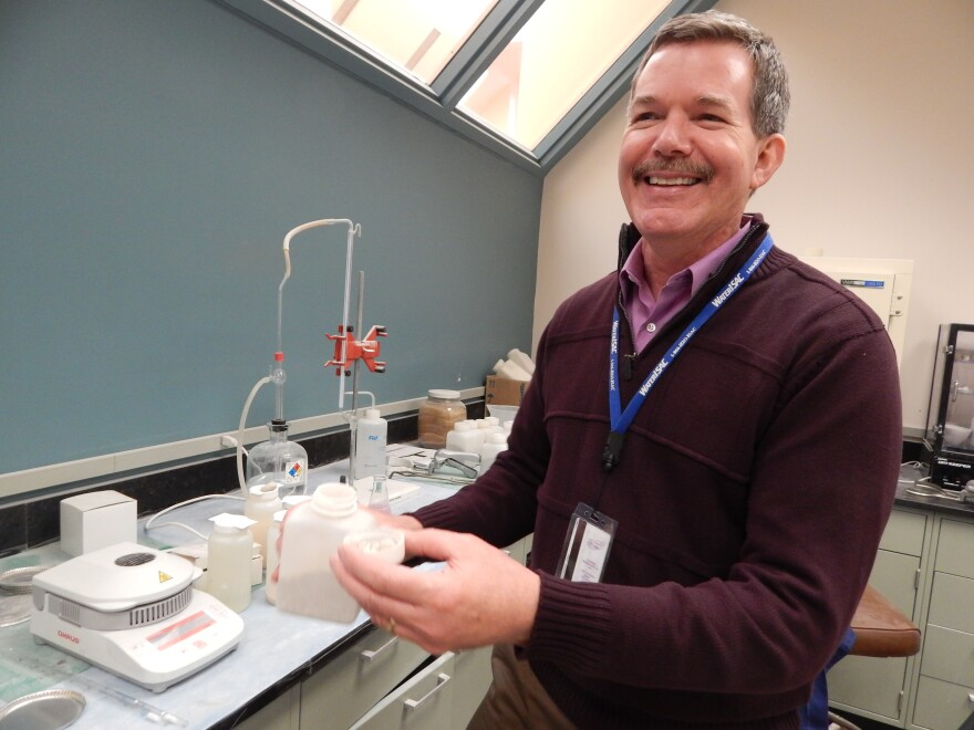 Phil Van Atta, head of water supply and treatment for the city of Dayton, shows off quicklime pebbles in the city's testing labs.