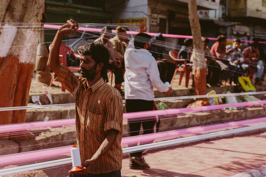 Bright kite strings stretch along a road in Gujarat.