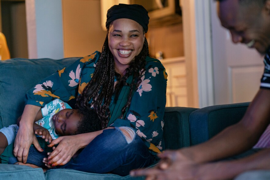 Samra Idris laughs with her husband as her son lies in her lap at their home. She says that people in Bellevue expect to succeed.