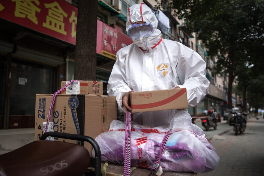 A worker in protective clothing with a package. In addition to encouraging couriers to wear this gear, the Chinese Center for Disease Control and Prevention has published a guide for the deliverymen, encouraging them to wash their hands and disinfect themselves before going home.