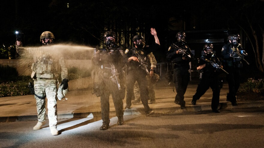 Federal officers use tear gas and other crowd dispersal munitions on protesters Friday outside the Multnomah County Justice Center in Portland, Ore.