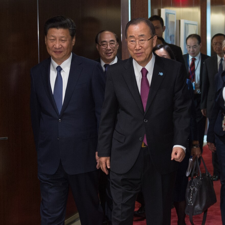 Chinese President Xi Jinping, left walks with U.N. Secretary-General Ban Ki-moon, on Saturday at U.N. headquarters in New York. At a U.N. conference, Xi pledged billions in Chinese aid to developing nations.