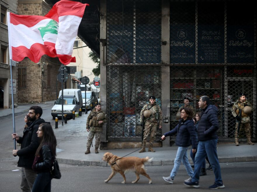 Army soldiers look on as Lebanese anti-government protesters march in Beirut in January.
