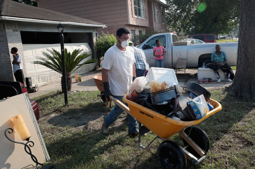 Volunteers from Performance Contractors help co-worker Cornell Beasley deal with Harvey-related water damage to his home in Houston on Friday.