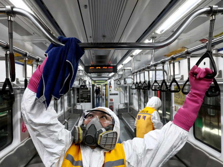 Disinfection workers spray antiseptic solution Wednesday in a subway car in Seoul, South Korea.