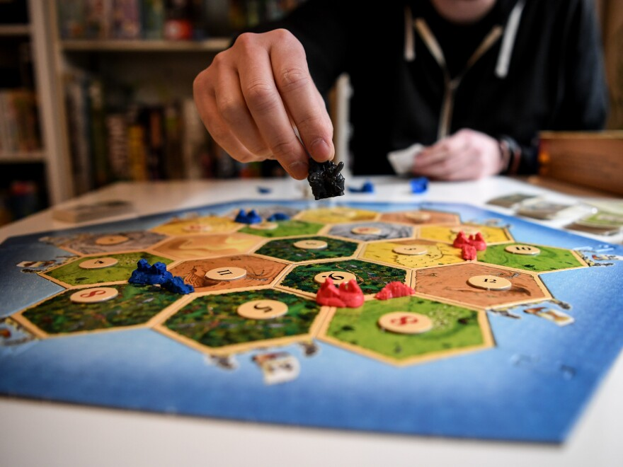"""Tim Overkamp shows the game """"The Settlers of Catan."""""""