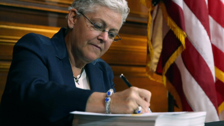 EPA Administrator Gina McCarthy signs new regulations targeting greenhouse gas emissions on Monday.