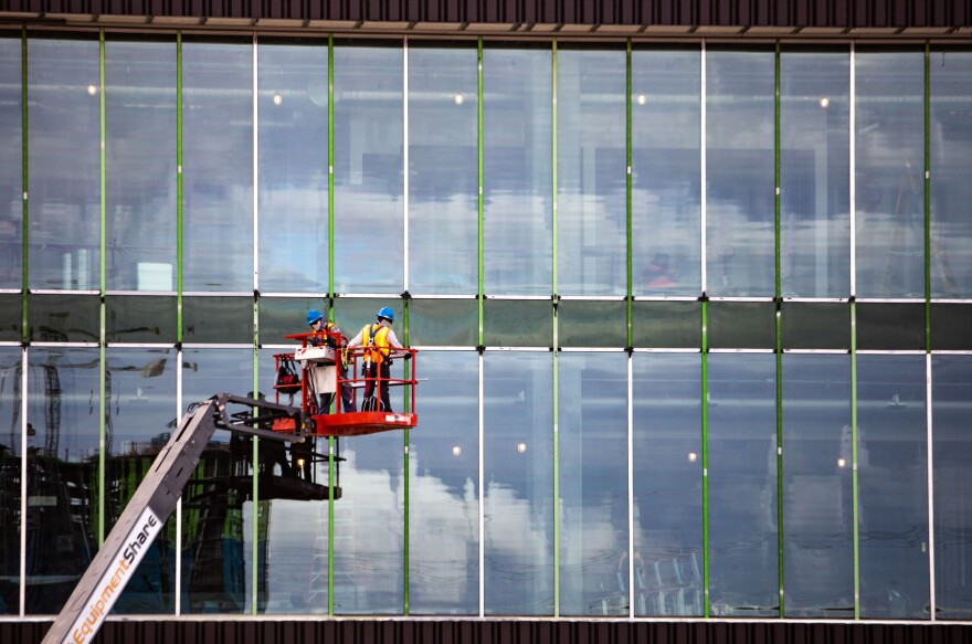 Workers work on the windows of the stadium.