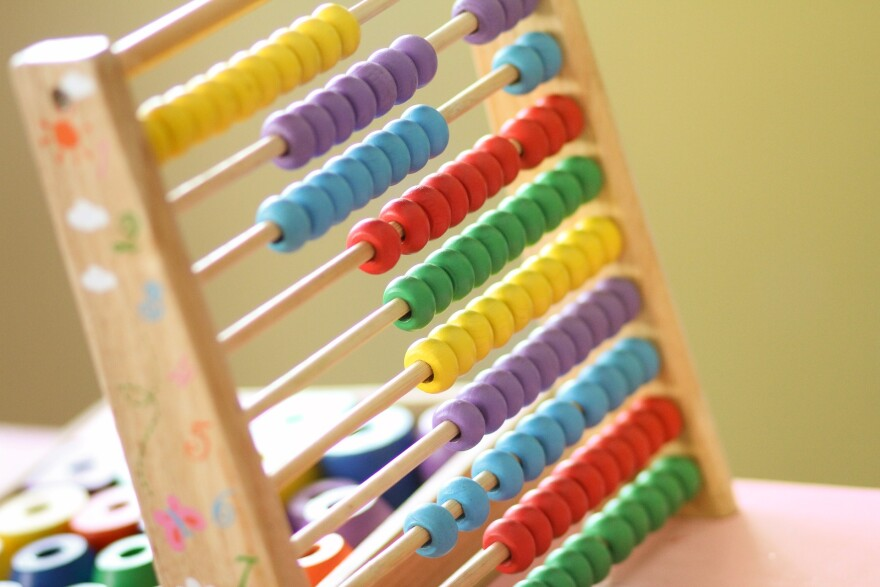A multicolored wooden abacus sits on a desk in a brightly lit room.