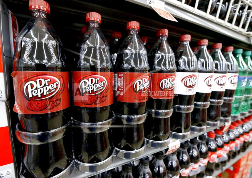 Bottles of Dr Pepper sit on a shelf in a market, Wednesday, Aug. 8, 2018.
