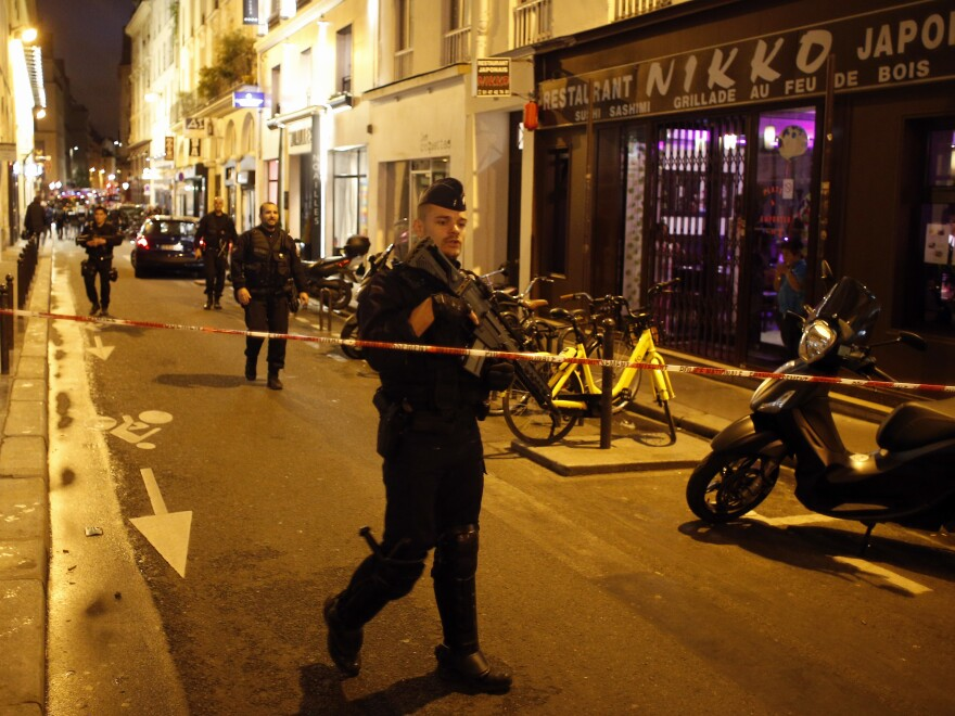 A police officer cordons off the area after a knife attack in central Paris on Saturday. The Paris police said the attacker was stopped by officers.