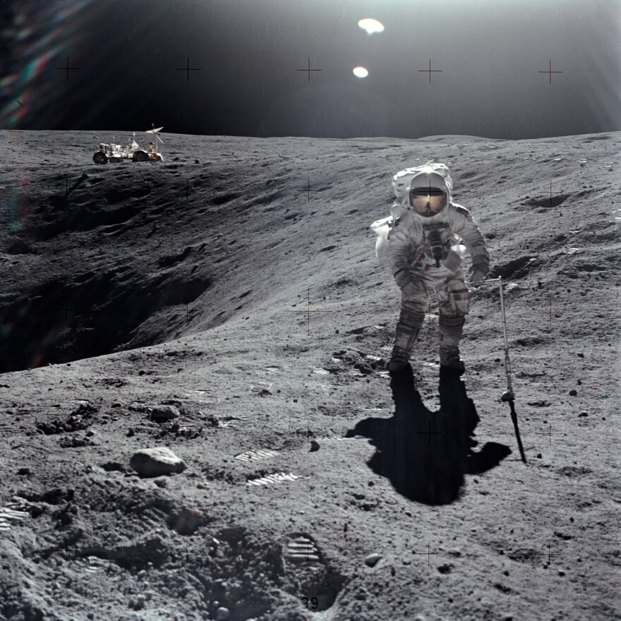Astronaut Charles M. Duke Jr. is photographed collecting lunar samples at Station No. 1 during the first Apollo 16 mission. Duke is standing at the rim of Plum crater. The parked lunar roving vehicle can be seen in the left background.