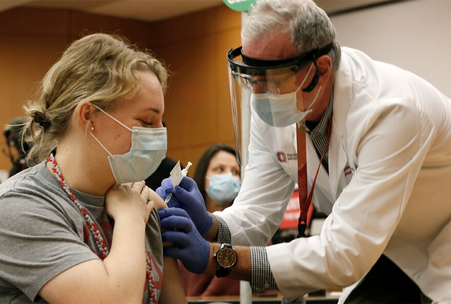 Ohio State employee Lauren Chisholm, left, receives a Pfizer-BioNTech COVID-19 vaccination from Robert Weber Monday, Dec. 14, 2020, in Columbus.