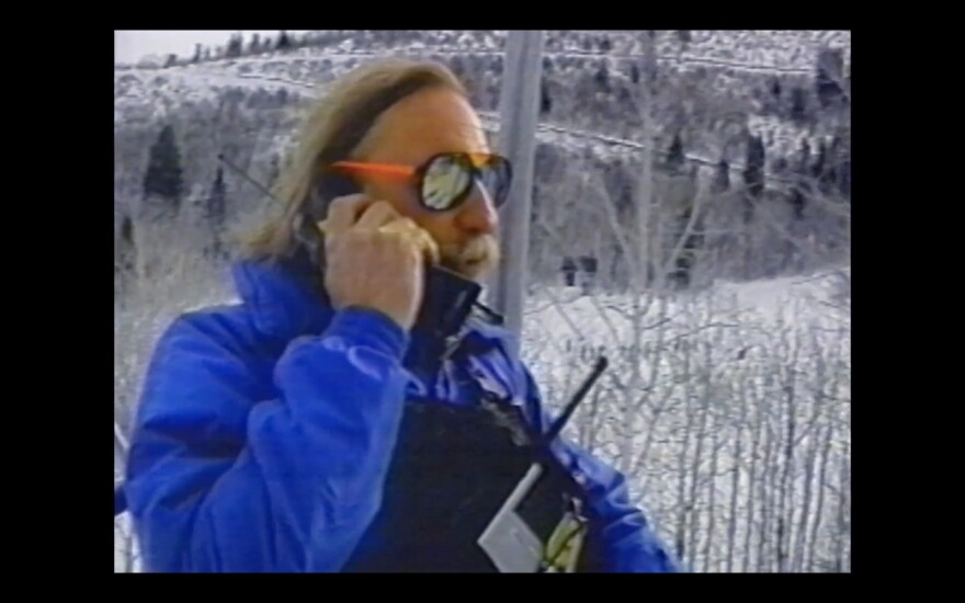 Photo of man on a snowy mountain in bright blue ski jacket and sunglasses, talking on old cell phone.