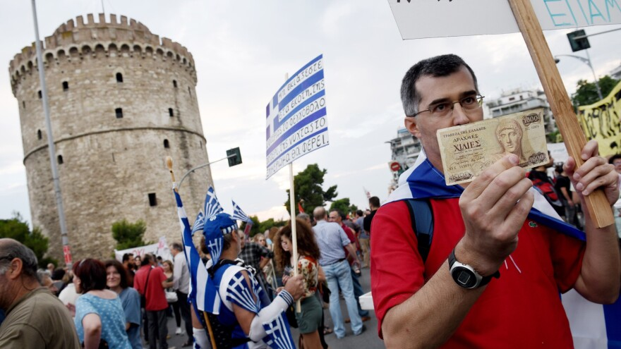 """A Greek demonstrator urges a """"no"""" vote in Sunday's referendum on whether Greece should accept international demands for additional financial austerity. He is holding an old 1,000 Greek drachma bank note during a rally in the northern Greek port city of Thessaloniki on Monday. Some Greeks say the country should leave the eurozone and go back to the drachma."""