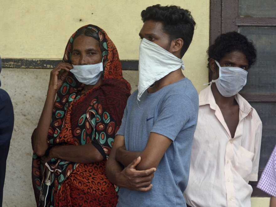 Indians standing in a line outside a hospital wear masks as a precautionary measure against the Nipah virus at the Government Medical College hospital in Kozhikode, in the southern Indian state of Kerala, on Monday.