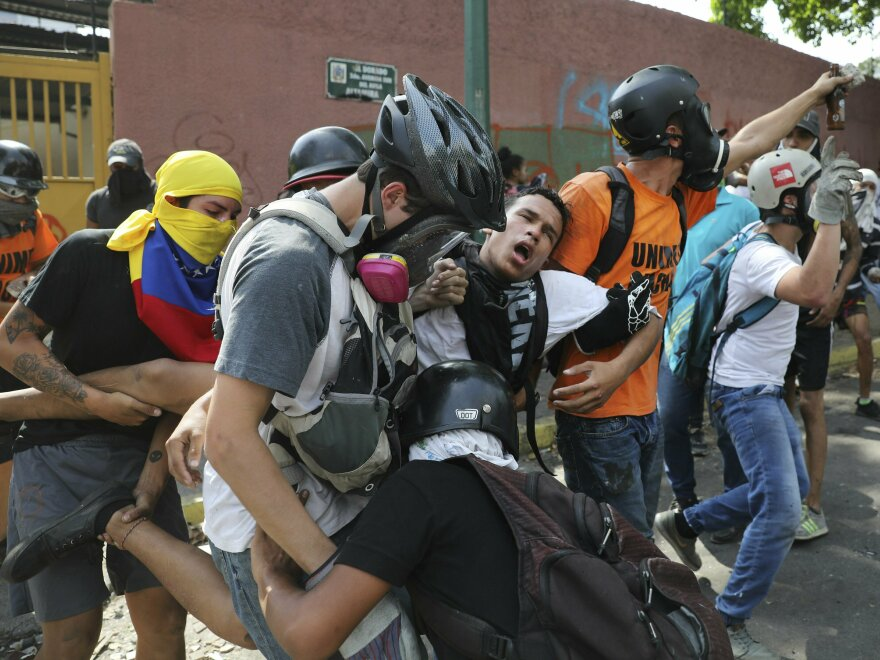 An anti-government protester is carried away after he was affected by tear gas launched by security forces, outside La Carlota airbase during clashes between the two sides in Caracas, Venezuela, on Wednesday.