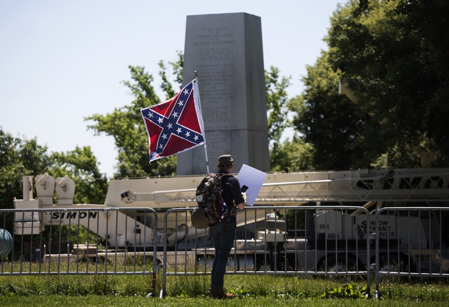 Brendan Koch, of Arnold, Missouri, looks at the Confederate Memorial after crews removed the top of it Thursday morning. June 8, 2017