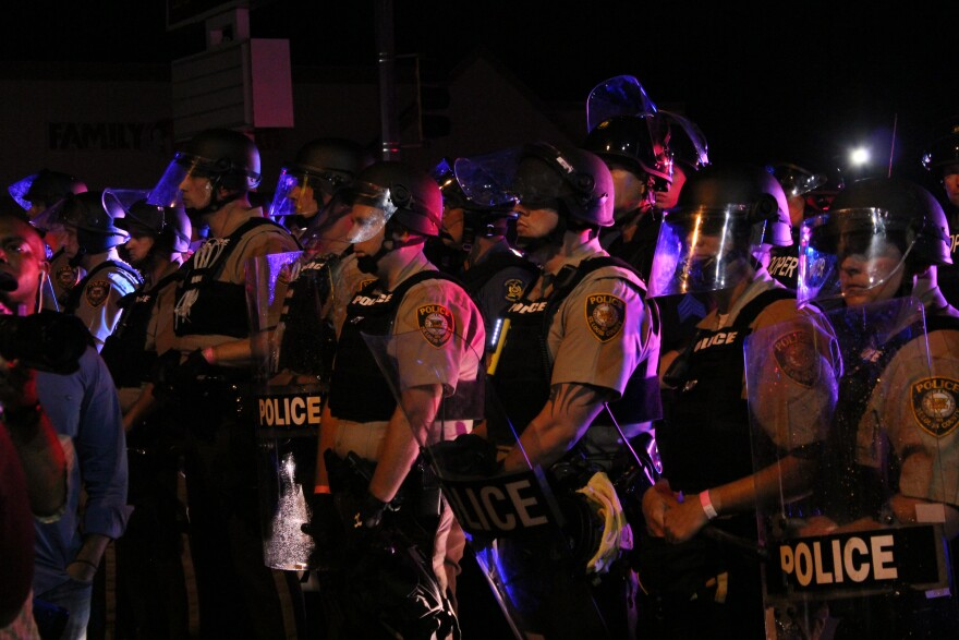 A line of police face off with protesters on West Florissant Ave., last Sunday night.