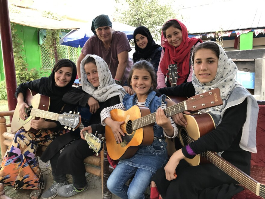"""The Miraculous Love Kids music school founder Lanny Cordola (top left) stands with Madina Mohammadi (top center), Mursal (top right) and other students outside their rehearsal space in Kabul. Their favorite song is """"Fragile"""" by Sting. """"What we're trying to do with music is not singing and dancing and fancy stuff,"""" Cordola says. """"You know, these are songs of compassion and hope and healing."""""""