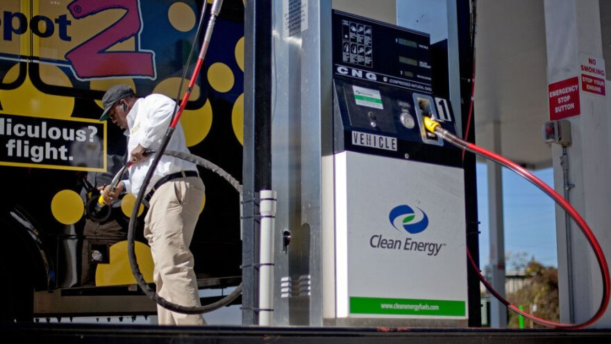 Bob Davis fills up his airport shuttle van at a natural gas pumping station in College Park, Ga. A growing number of companies are considering converting their vehicle fleets to natural gas.