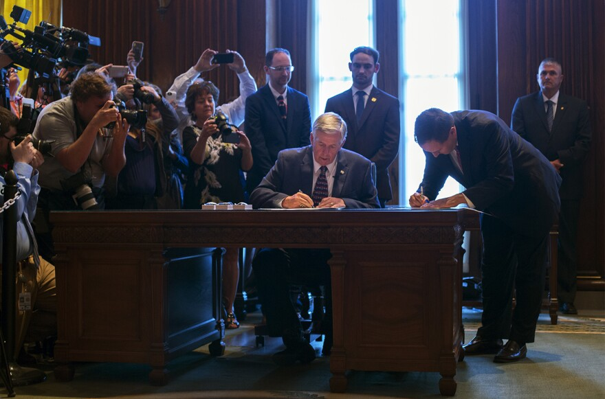 Missouri Gov. Mike Parson signs paperwork after taking his oath of office. June 1, 2018