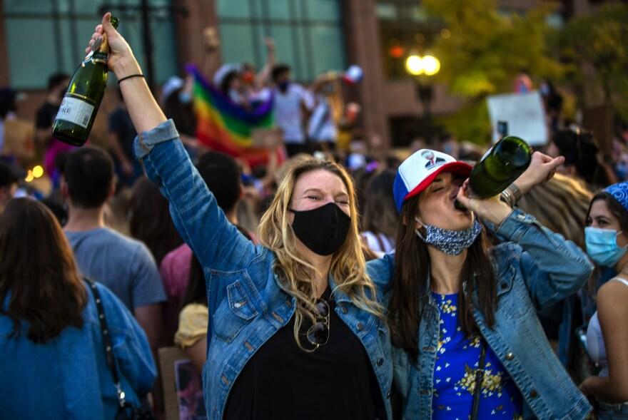 <strong>BOSTON</strong>: Two women celebrate Joe Biden's presidential victory, drinking bottles of champagne on Boylston Street.