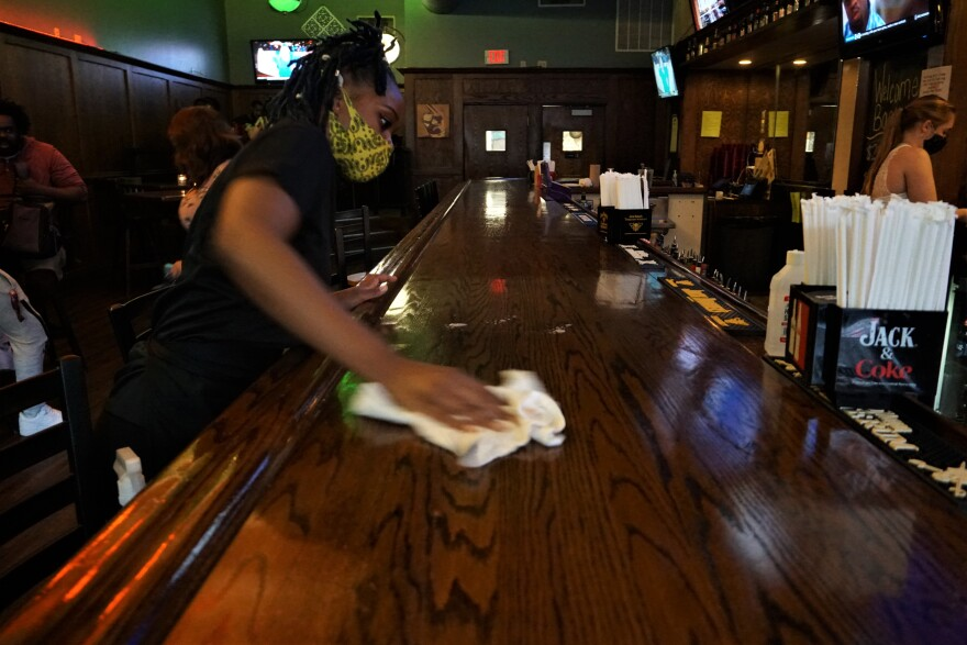 Server and bartender Mencia Haymon wipes counters down with disinfectant at Flannery's Pub in downtown St. Louis. Flannery's has spaced tables far apart. Servers and other workers wear masks to limit the spread of the coronavirus.