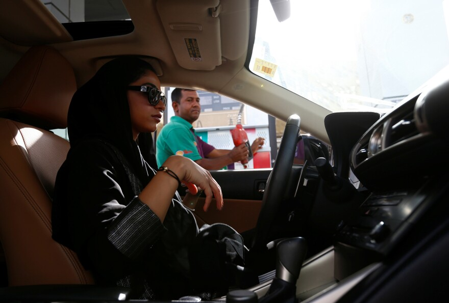 Majdooleen, one of the first women allowed to drive in Saudi Arabia, refuels her car as she drives to work in Riyadh on Sunday.