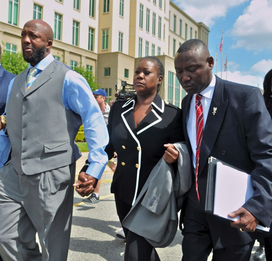 Tracy Martin and Sybrina Fulton, the parents of Trayvon Martin, walk with attorney Benjamin Crump and others as they leave the Seminole County courthouse after the bond hearing for George Zimmerman.