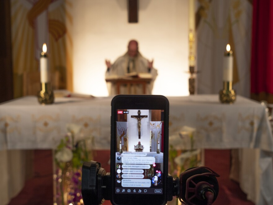 Rev. Nicolás Sánchez is seen on his iPhone used to livestream Easter Vigil Mass at St. Patrick's Catholic Church in North Hollywood, Calif., which was closed under the state's coronavirus lockdown order.