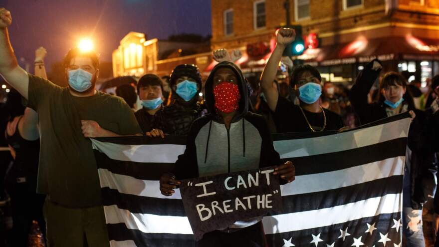 Protesters gather Tuesday near where Floyd died in police custody in Minneapolis. One of them displays Floyd's final words, recalling those made famous by Eric Garner when he died in 2014 in New York City.