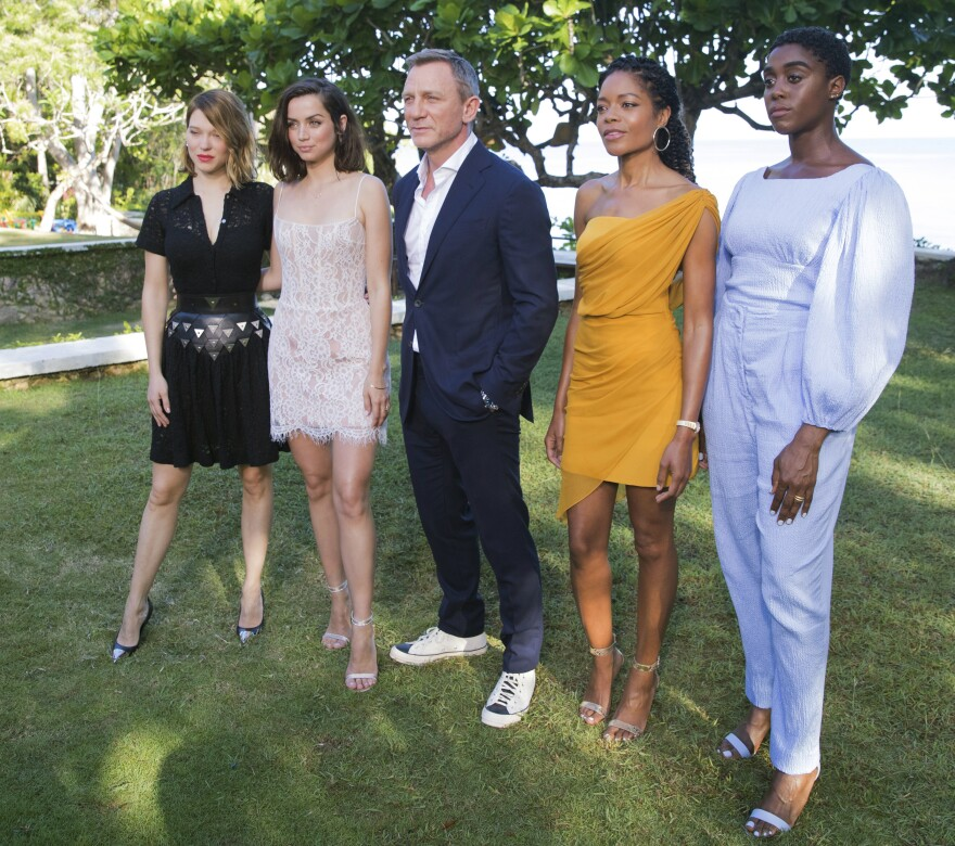 The cast of <em>No Time To Die</em> in a publicity photo taken April 2019, on location in Oracabessa, Jamaica. From left: Lea Seydoux, Ana de Armas, Daniel Craig, Naomie Harris and Lashana Lynch. The film, originally scheduled for theatrical release in April 2020, has been postponed for the third time because of the pandemic.