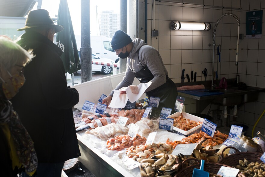 Benoit Celino sells fish to a customer at the fish market in Boulogne-sur-Mer.
