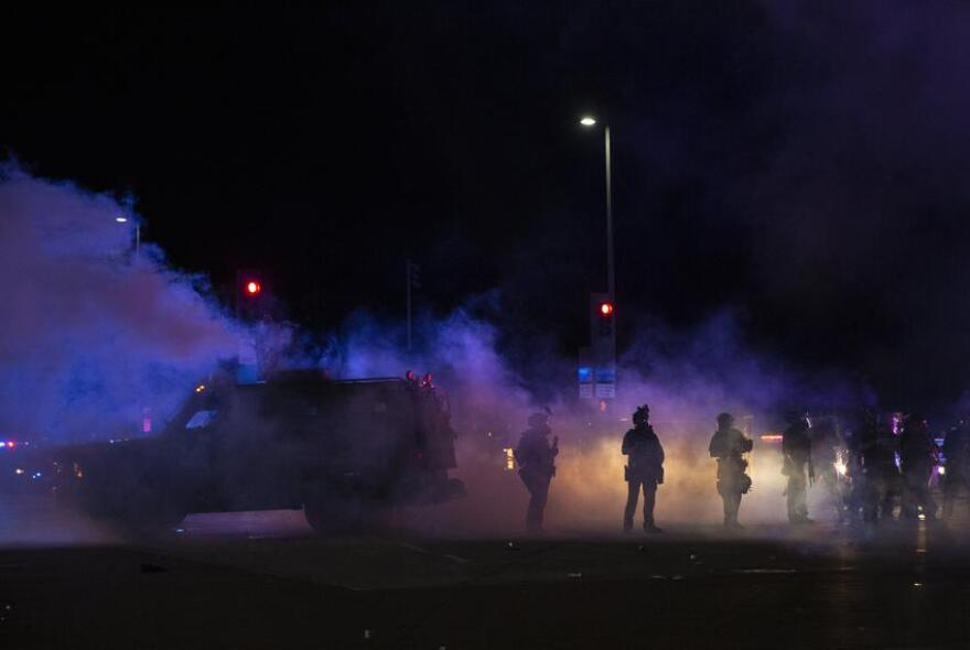 Dallas Police tactical officers stand among a cloud of tear gas and smoke after they fired it at protesters during a march against police brutality on May 29.