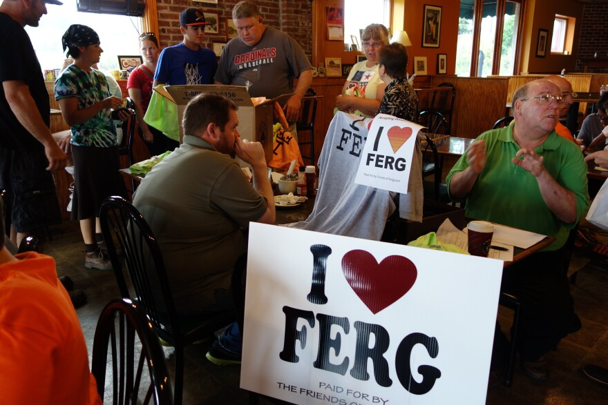 """Ferguson residents pass out """"I heart Ferg"""" yard signs at a local coffee shop."""