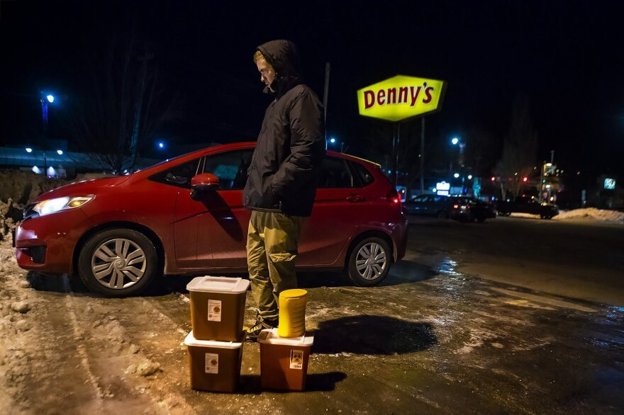 Jesse Harvey, founder of the Church of Safe Injection, stands in a Denny's parking lot in Auburn, Maine, alongside four sharps containers filled with used needles collected from drug users around the neighboring city of Lewiston.