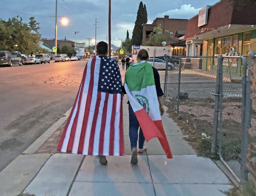 A couple draped in U.S. and Mexican flags leave a rally in El Paso on Sunday night. They'd just seen a mural unveiled by the family of a victim from last year's shooting in Parkland, Florida. The unveiling had been planned long before Saturday.